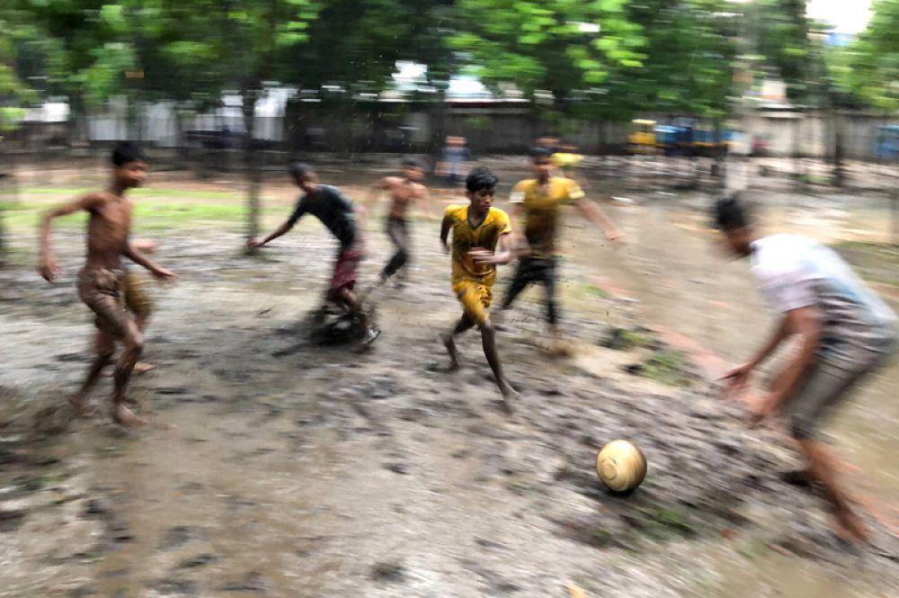 Мальчики играют в футбол во время дождя в Дакке, Бангладеш.