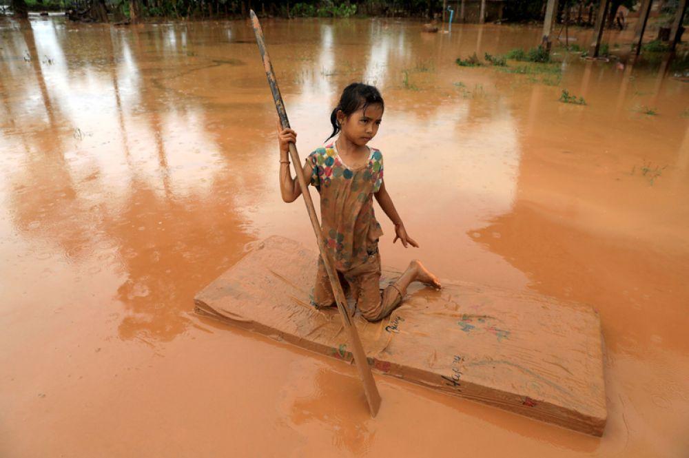 Девочка использует матрас в качестве плота после наводнения, вызванного обрушением дамбы в провинции Аттапу, Лаос.