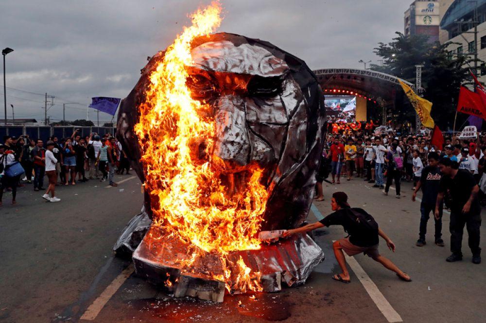 Активисты сжигают изображение президента Филиппин Родриго Дутерте в городе Кесон, Манила, Филиппины.