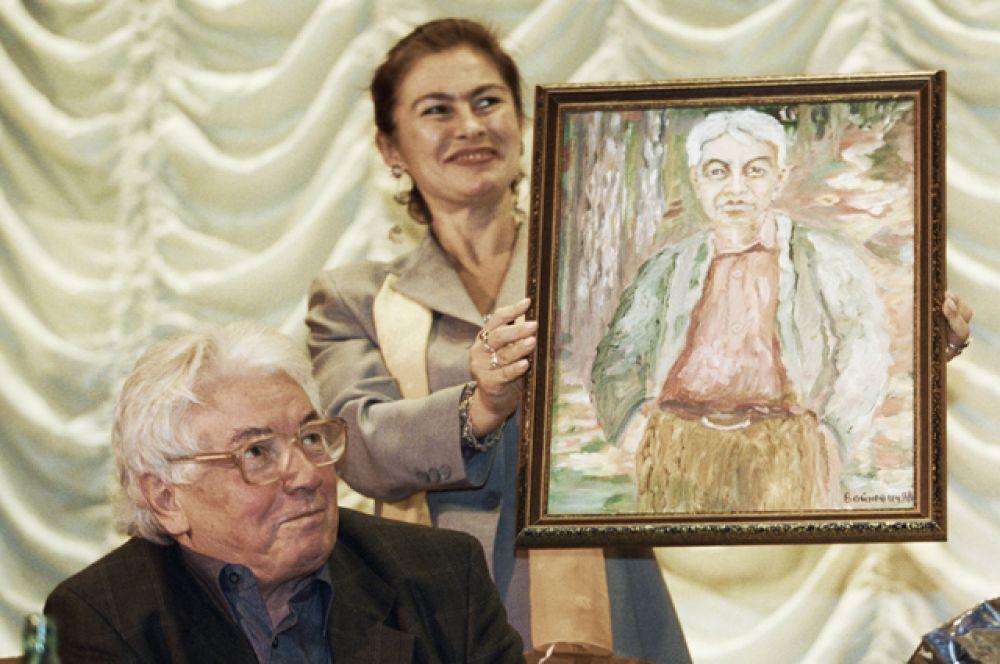 Писатель Владимир Войнович на презентации своей книги. Женщина держит автопортрет писателя.