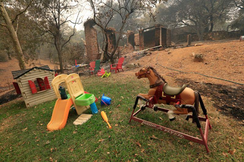 Детские игрушки рядом с домом, сгоревшим в результате пожара.