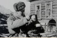 Воин Красной армии кормит ребёнка.