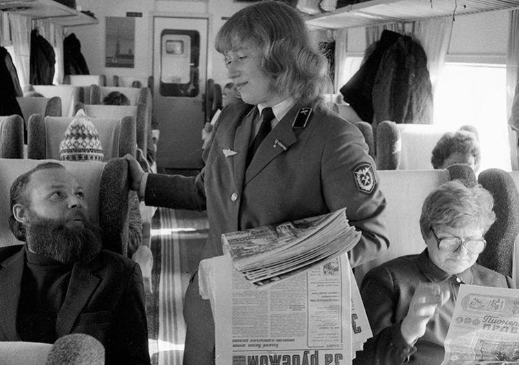 Проводница предлагает пассажирам свежие газеты в вагоне скоростного экспресса «ЭР-200» «Москва – Ленинград». 1984 год.