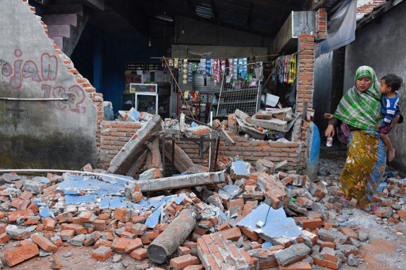 Женщина пробирается через обломки своего дома в Ленданге, Ломбок.