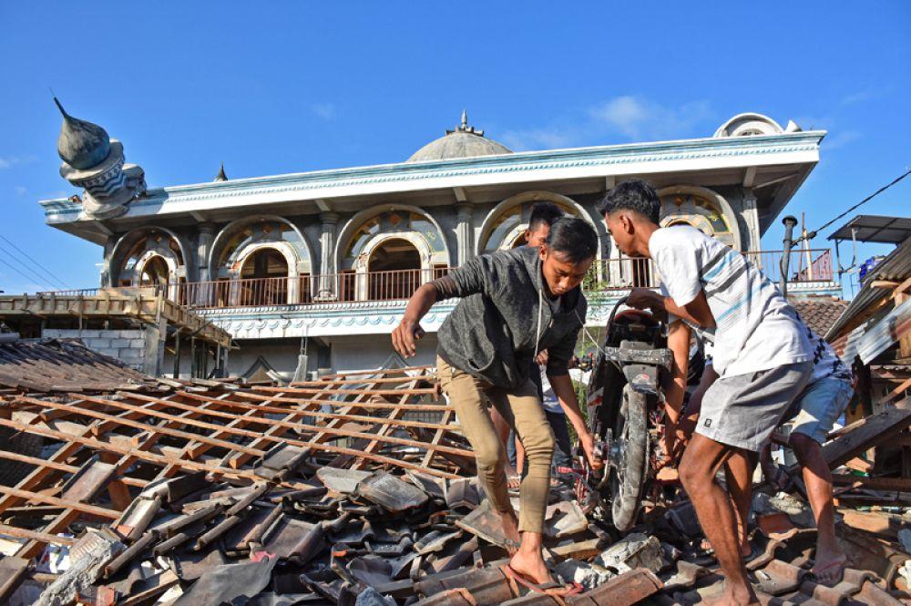 Жители вытаскивают имущество из разрушенного дома после сильного землетрясения в Гунунгсари, Западный Ломбок.