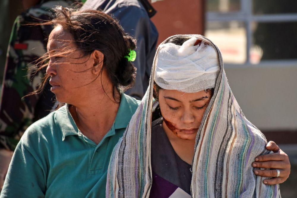Женщина, пострадавшая во время землетрясения, около больницы Северного Ломбока в Танджунге.