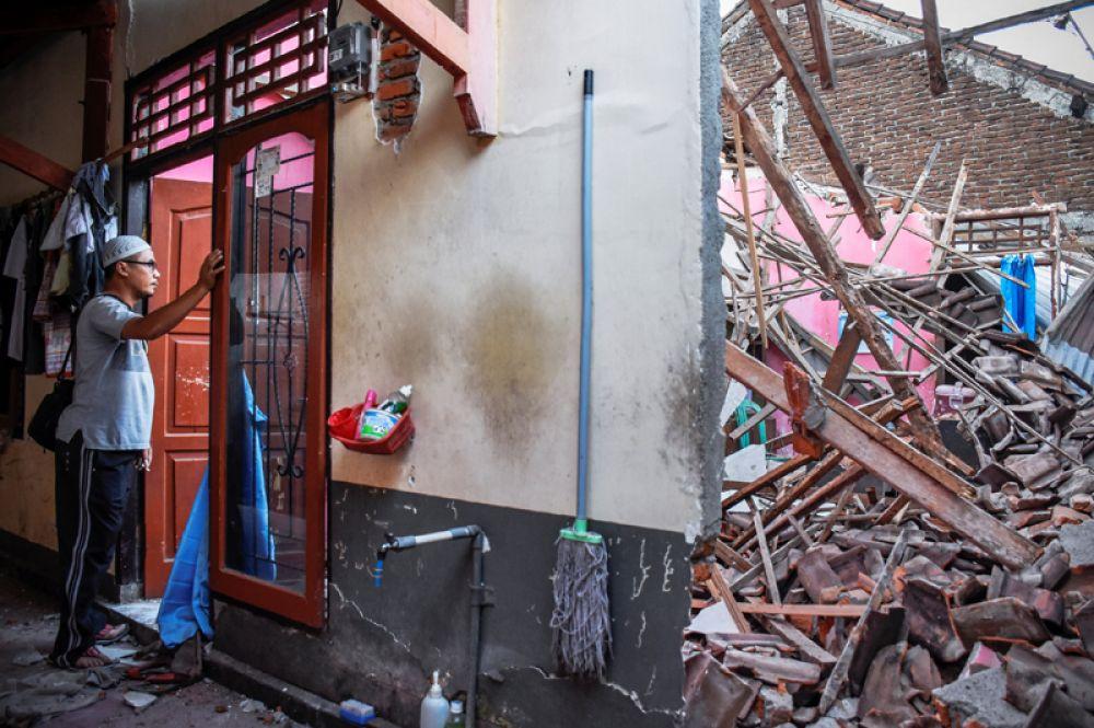 Мужчина около своего дома, разрушенного в результате сильного землетрясения в Ленданге.