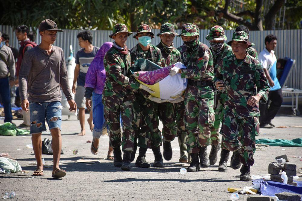 Спасатели несут тело жертвы землетрясения к машине скорой помощи, Северный Ломбок.