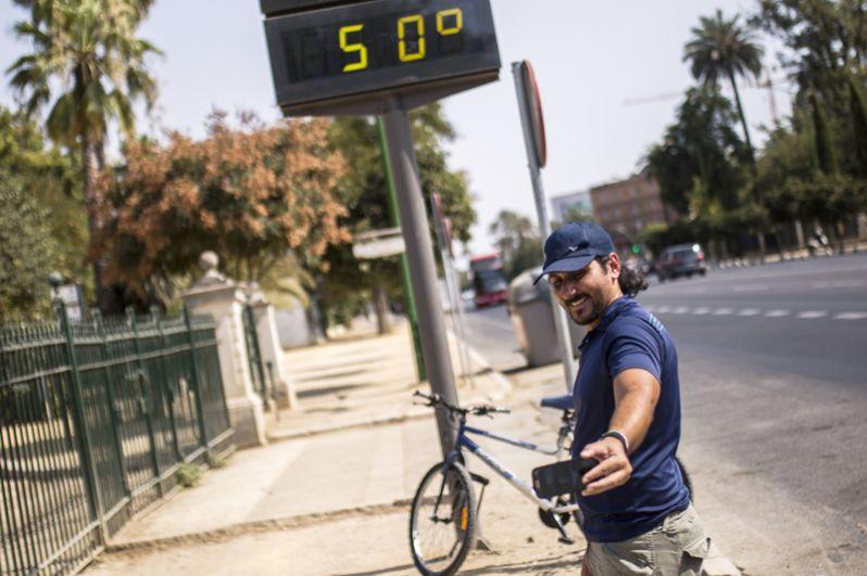 Мужчина фотографируется у электронного табло, которое показывает температуру +50 градусов по Цельсию на улицах Севильи, Испания.