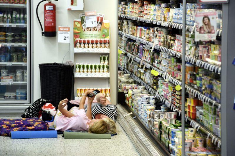 Покупатели отдыхают в продуктовом магазине в жаркий день в Хельсинки, Финляндия.