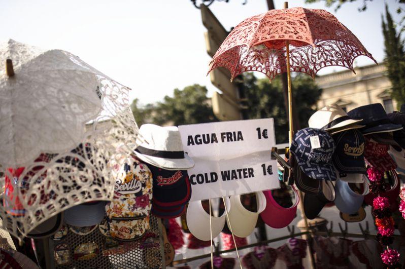 Продажа зонтиков, кепок и шляп на улице Севильи, Испания.