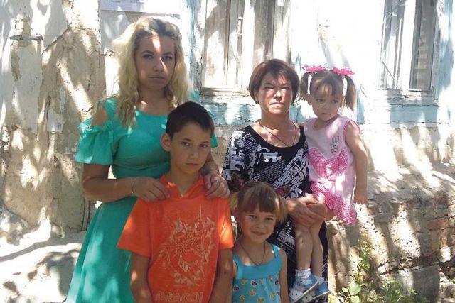 Наталья Фисенко с детьми возле старого дома.