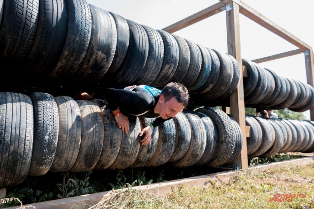 Участникам приходилось преодолевать несколько препятствий - например, проползти между шинами.