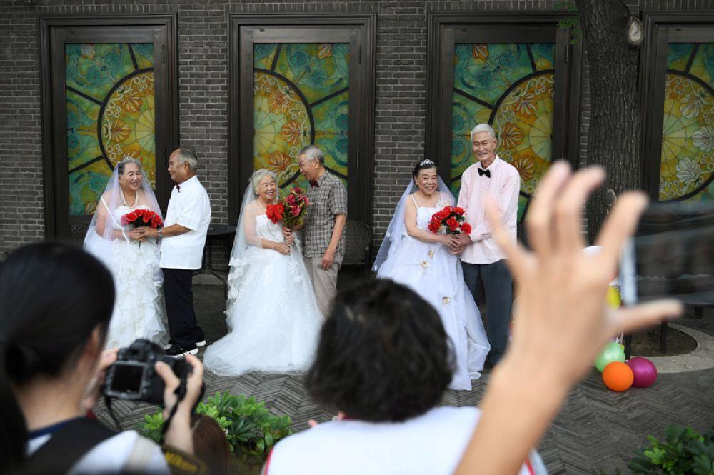 Пожилые пары, которые женаты уже более 50 лет, воссоздают свои свадебные фотографии перед праздником Ци Си или Дня влюбленных, Тяньцзинь, Китай.