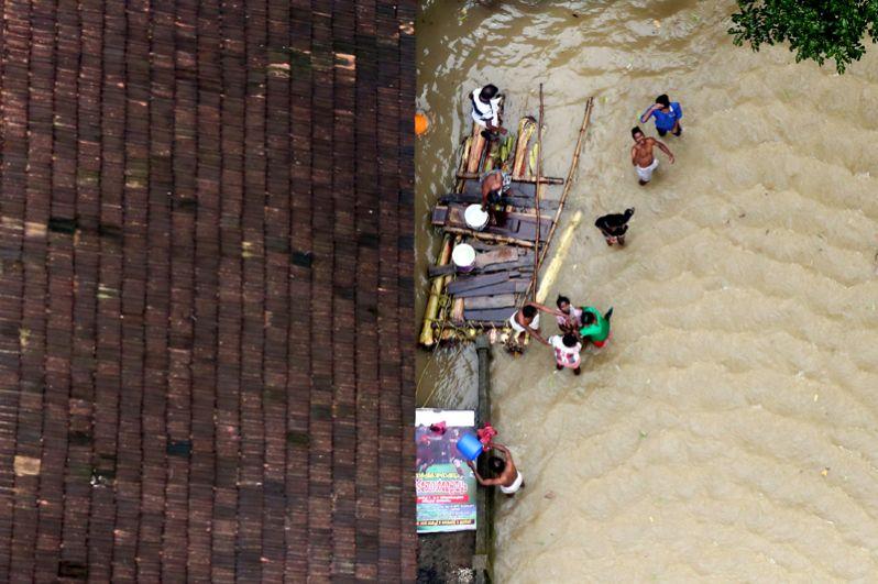 Люди на импровизированном плоту ждут помощи спасателей в штате Керала.