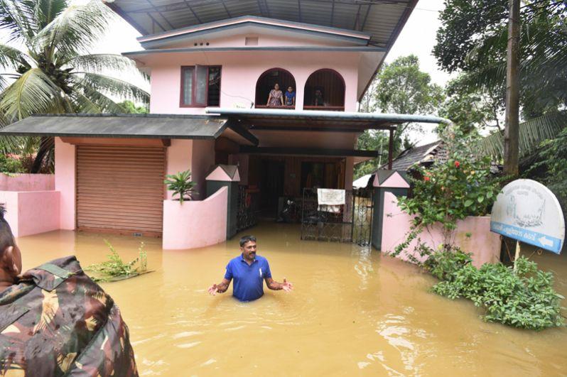 Мужчина во дворе своего дома во время наводнения в Алаппуже в штате Керала.