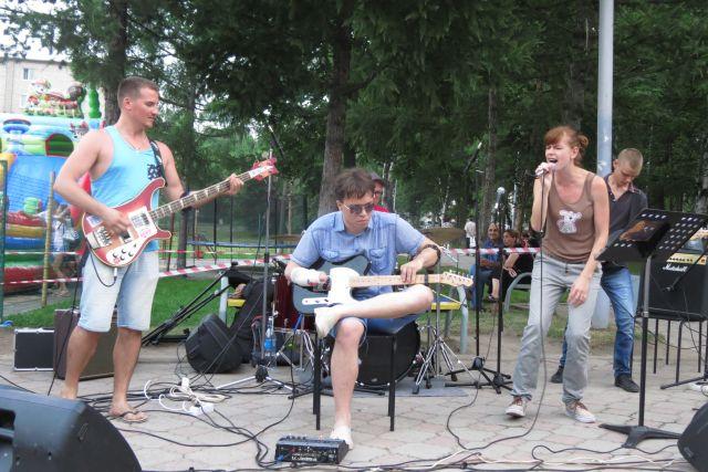 Евгений Некрасов на концерте в Артёме - в центре с гитарой.