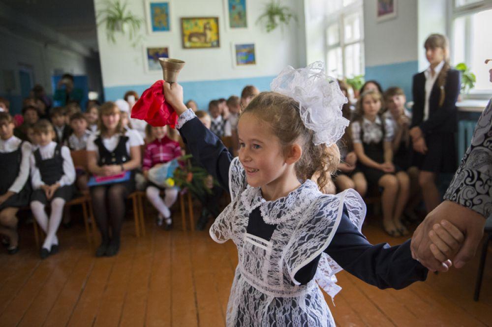 Первоклассница со звонком во время торжественной линейки в школе в селе Кирилино Омской области.