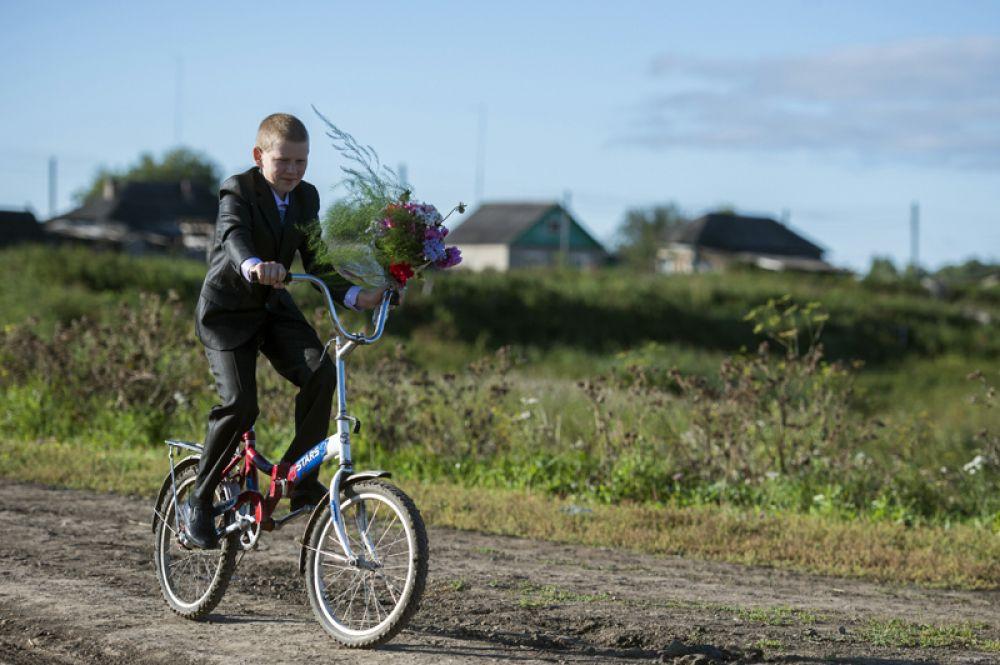Мальчик с цветами едет в школу в селе Кирилино Омской области.
