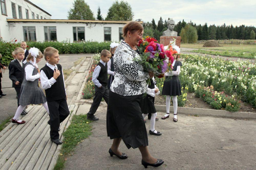 Учительница начальных классов школы деревни Баженово Омской области Нина Лукина с учениками.