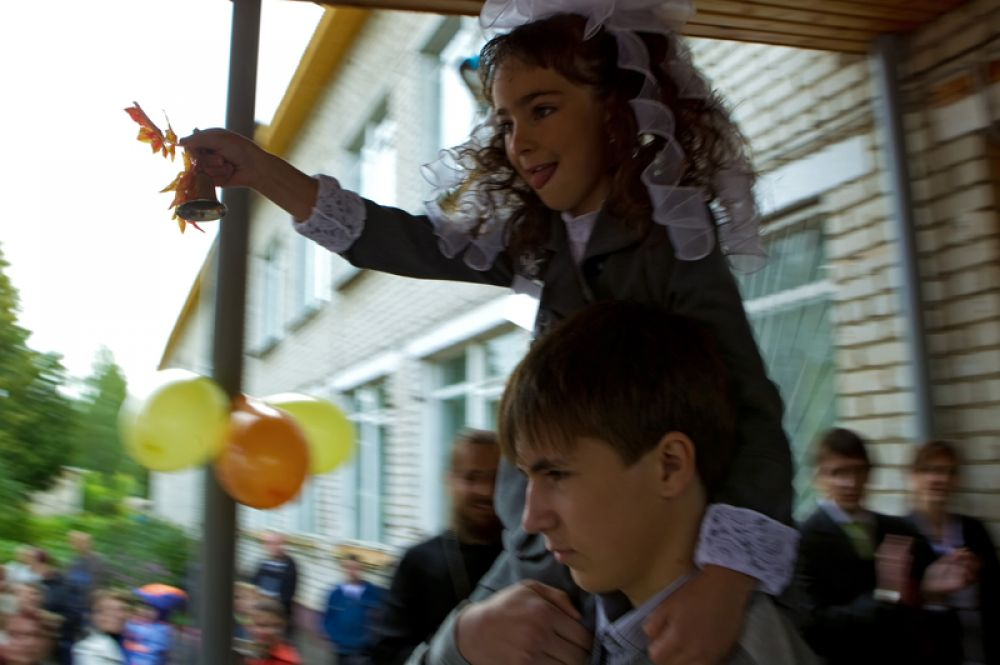 Первоклассница с колокольчиком на плече у старшеклассника школы села Пречистое Ярославской области.
