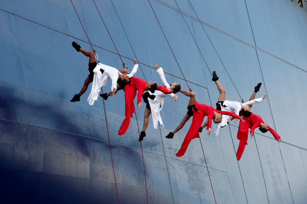 Группа танцоров выступает во время церемонии спуска на воду сухогруза «Антуан де Сент Экзюпери» в Гавре, Франция.