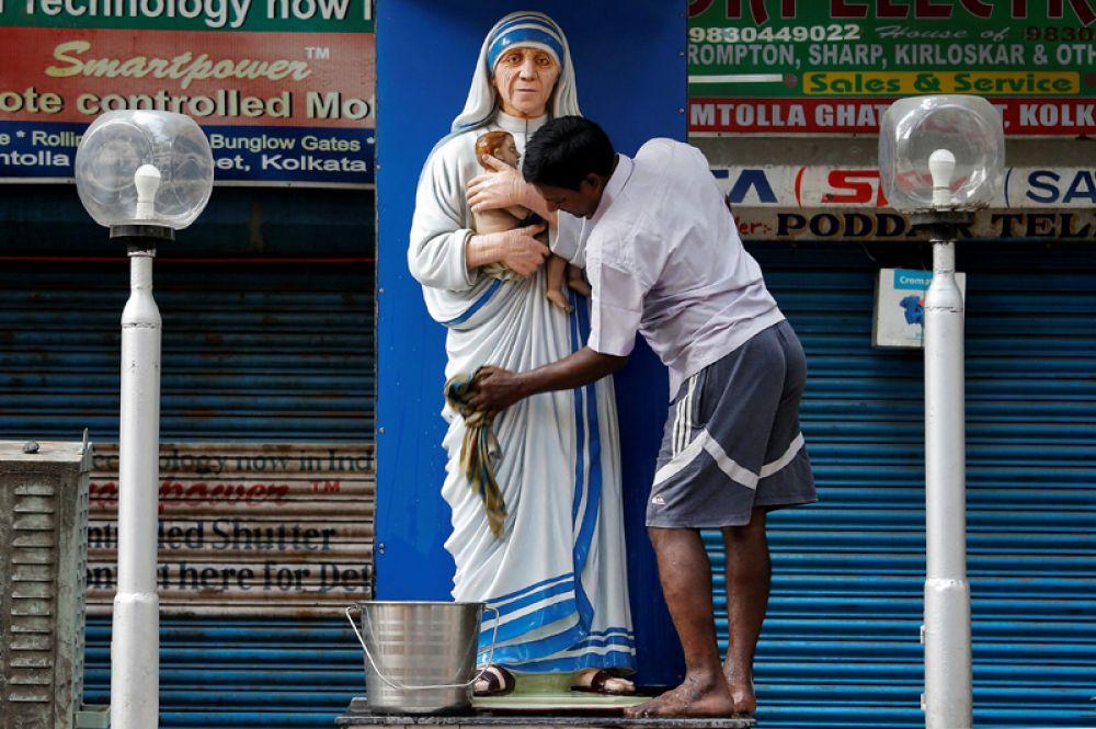Мужчина моет статую Матери Терезы перед годовщиной ее смерти, Калькутта, Индия.