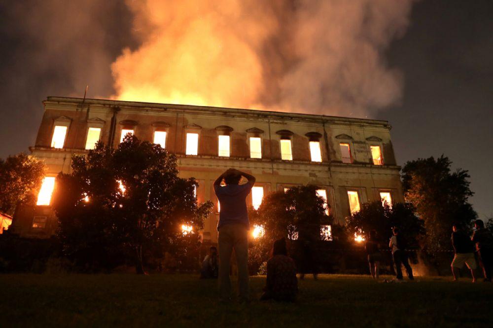 Жители Рио-де-Жанейро смотрят на горящее здание Национального музея, Бразилия.
