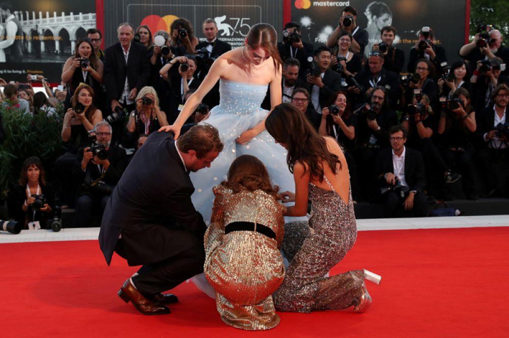 Ассистенты поправляют платье актрисы Рэффи Кэссиди на 75-м Венецианском международном кинофестивале.