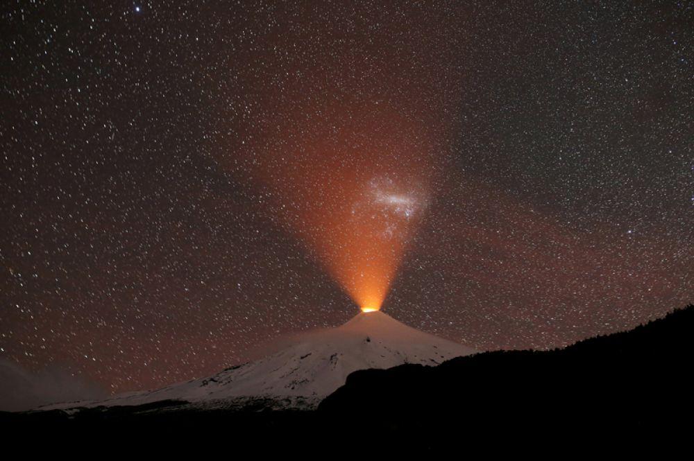 Ночной вид на вулкан Вильяррика из города Пукон, Чили.