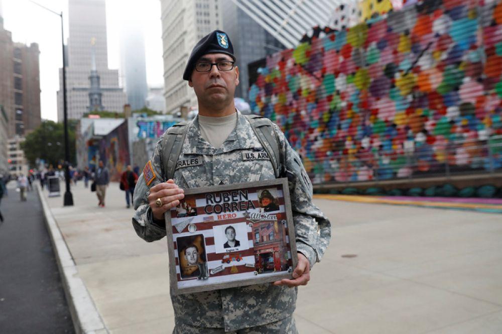 Сержант армии США с портретом своего двоюродного брата перед началом церемонии, посвященной 17-й годовщине терактов 11 сентября, Нью-Йорк.