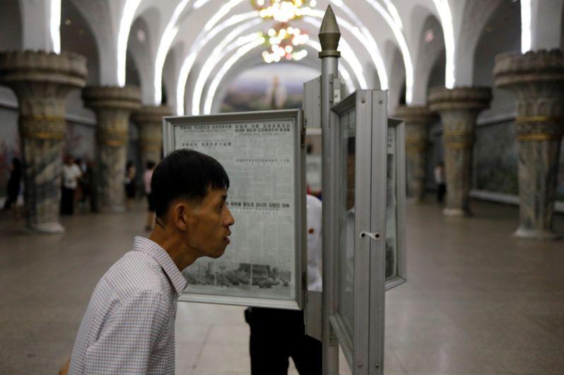 Пассажиры читают газеты на станции метро в Пхеньяне.
