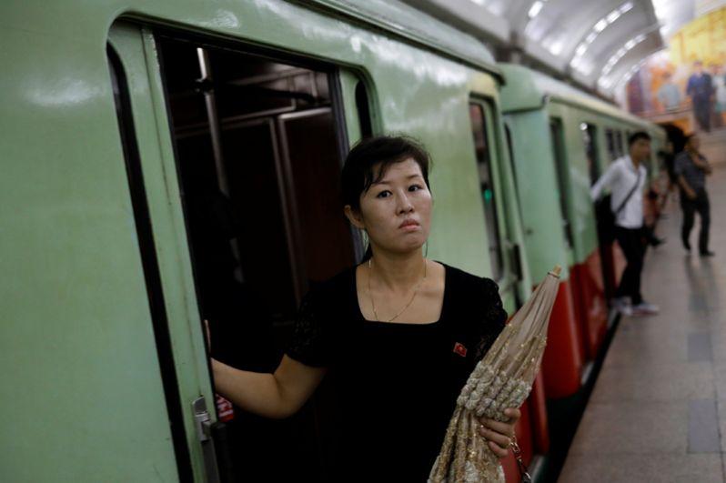 Девушка выходит из вагона поезда в пхеньянском метрополитене.