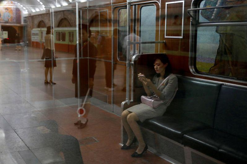 Девушка в вагоне поезда в пхеньянском метрополитене.