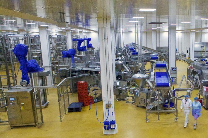 В подготовительном цехе люди работают только на участке набивки колбас. Они контролируют процесс через компьютер: устанавливают вес, длину изделия и заменяют пленку, из которой делается оболочка, если она заканчивается. Затем колбасы подвешивают на палки. Огромные механические руки (на фото — слева в синих чехлах) устанавливают палки на вертикальные рамы.