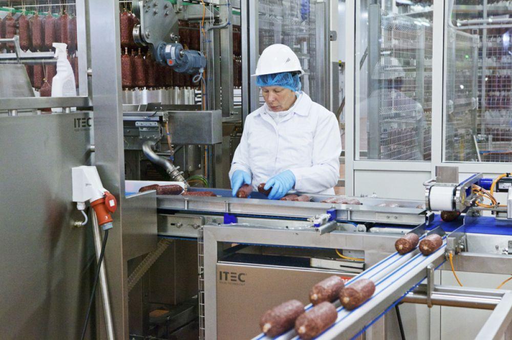 В упаковочном цехе манипуляторы срезают с оболочки петли и укладывают батоны в ячейки вакуумных упаковочных машин. По мере движения колбас по транспортёру операторы контролируют их качество.