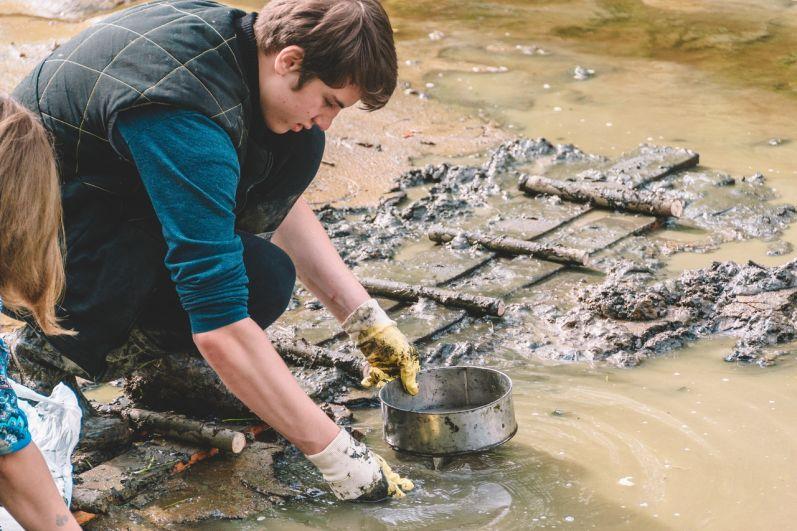 Находки складывают в сито и плавными движениями по воде освобождают их от глины.