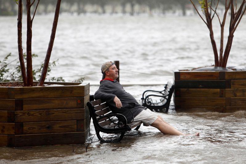 Мужчина на скамейке в затопленном парке в Уилмингтоне, Северная Каролина.