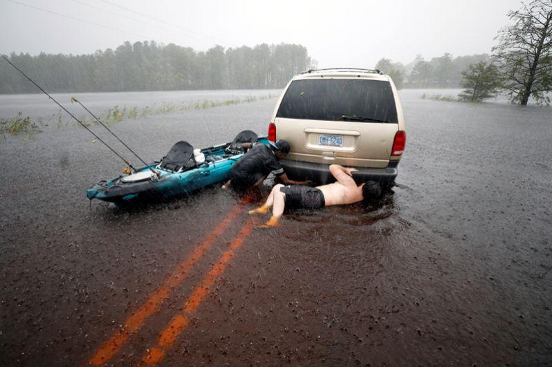 Мужчины пытаются освободить застрявшую машину в Бойлинг Спринг Лейкс, Северная Каролина.