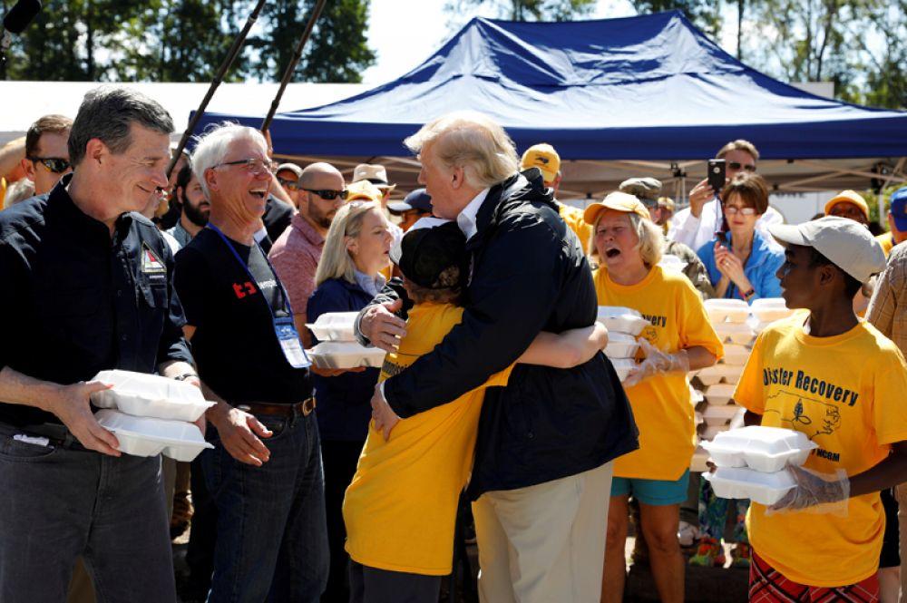Президент США Дональд Трамп обнимает мальчика во время визита в Нью-Берн, штат Северная Каролина, пострадавшему от урагана «Флоренс».