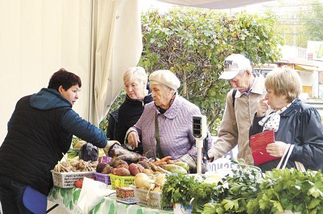 Людмила Головина, которая выращивает сортовой картофель, помогает выбирать овощи покупателям.