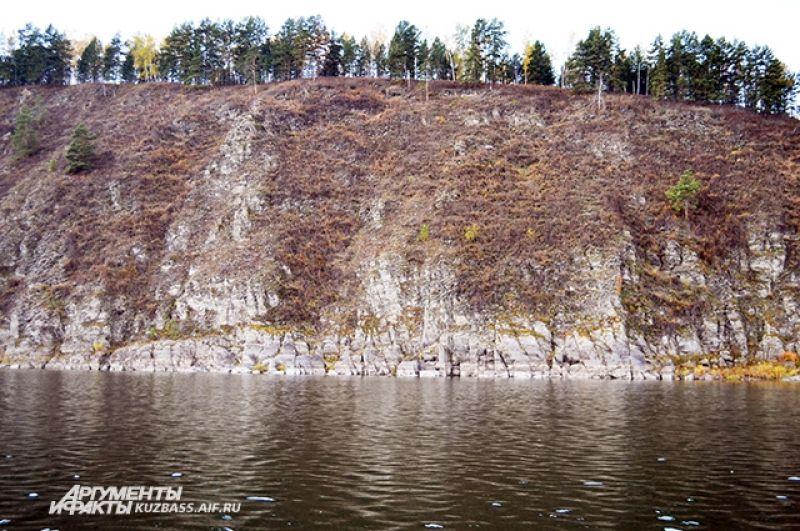 Местами берег Томи напоминает берег фьорда. И вдоль скал на север от Новоромановской писаницы мимо Висячего камня можно попасть на Тутальскую писаницу.