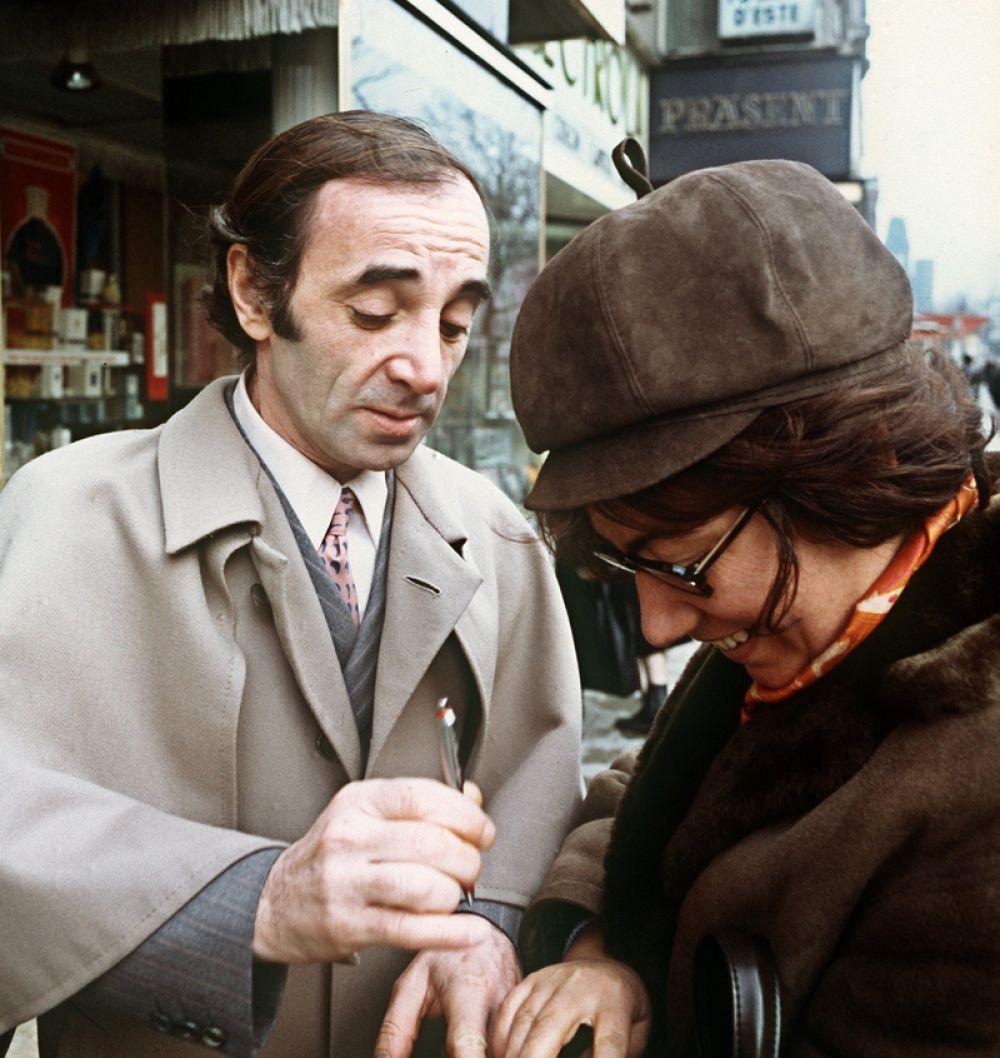 Шарль Азнавур раздает автографы во время визита в Берлин.