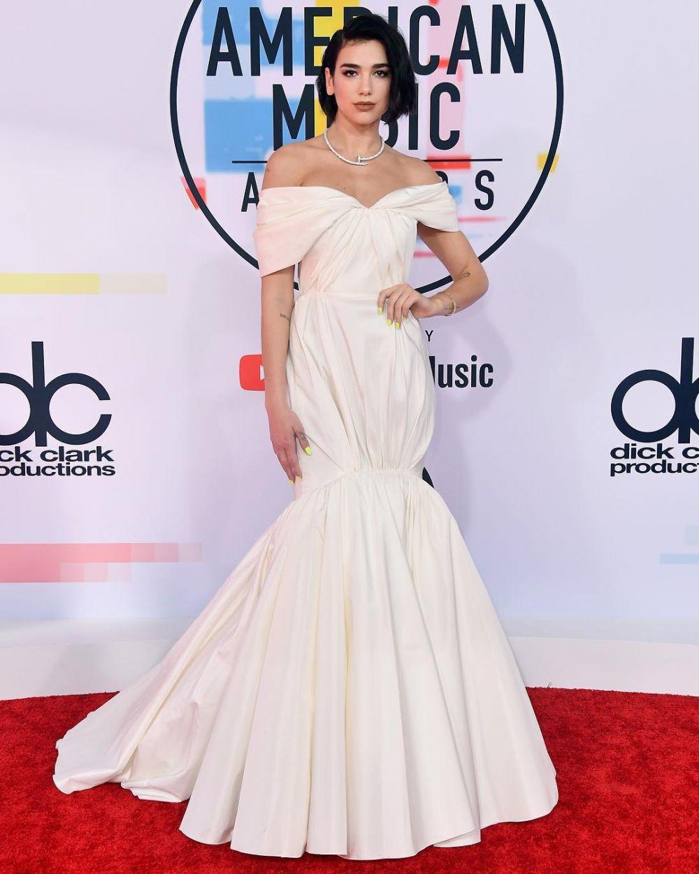 Британская певица Дуа Липа надела белое платье необычного кроя очень смахивающее на обертку от конфеты.