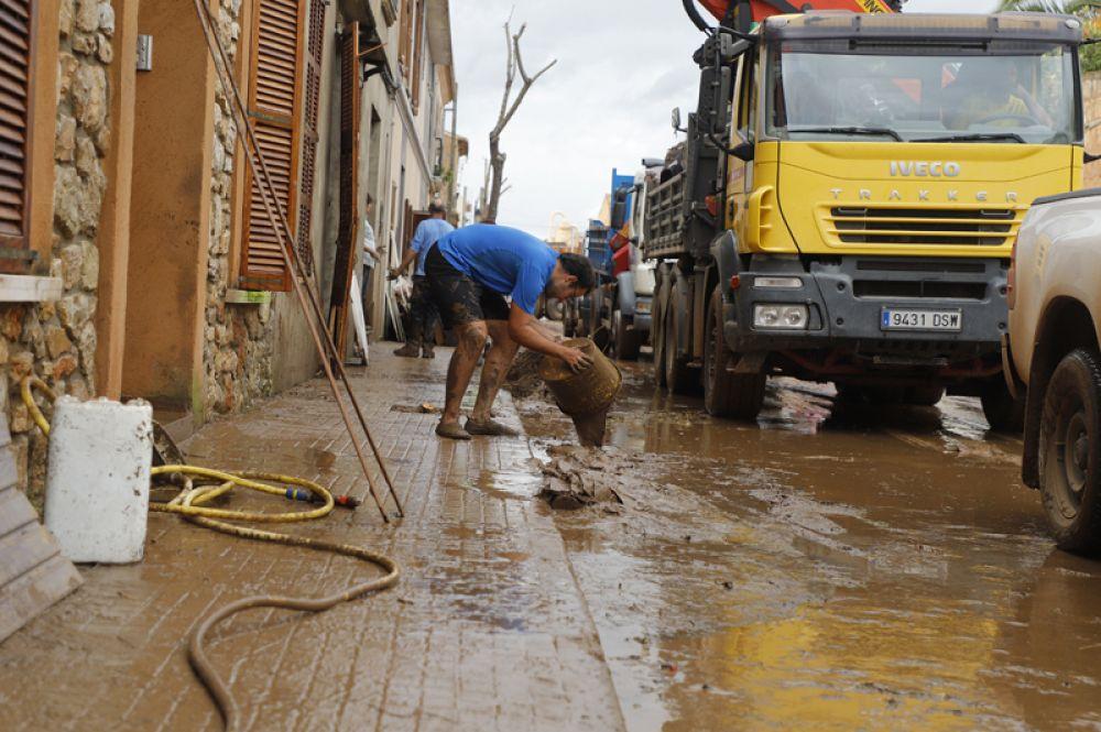Мужчина убирает грязь и мусор из своего дома после наводнения.