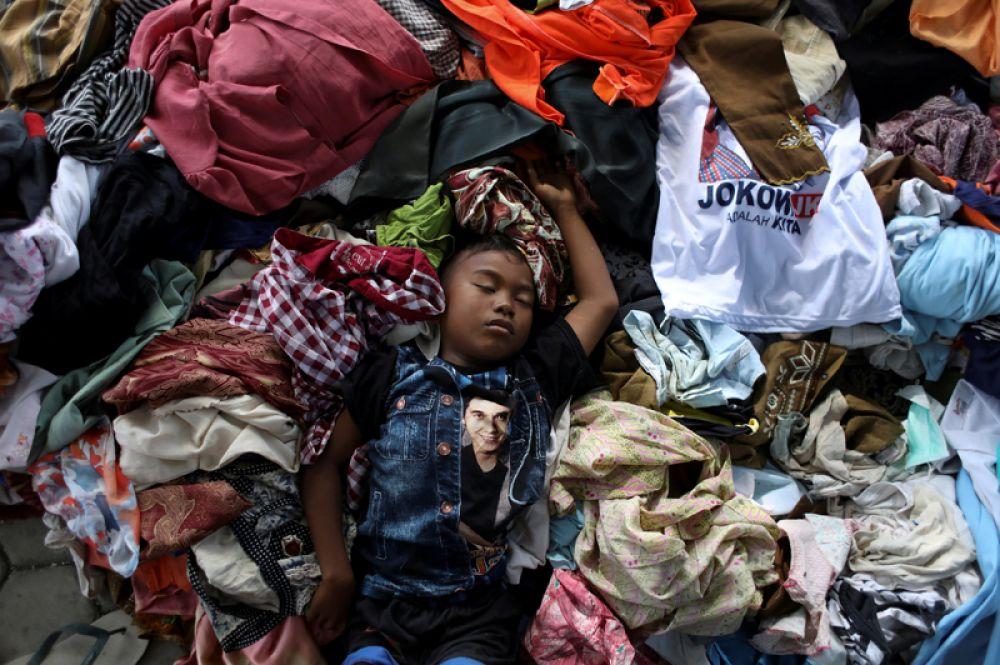 Мальчик спит в куче одежды в лагере для жертв землетрясения и цунами в Палу, Индонезия.