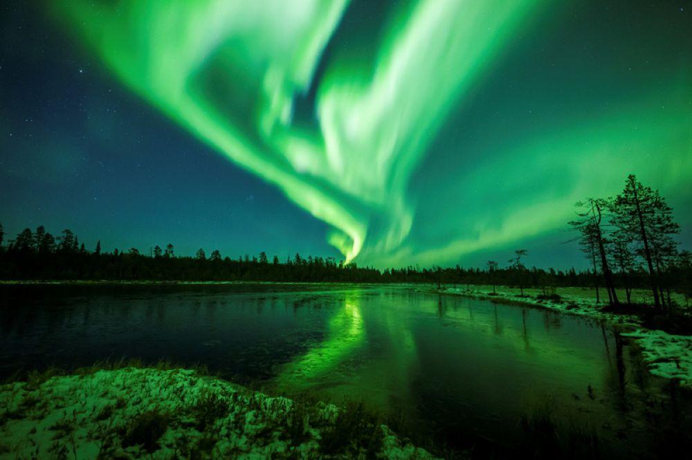 Северное сияние в небе над городом Рованиеми, Финляндия.