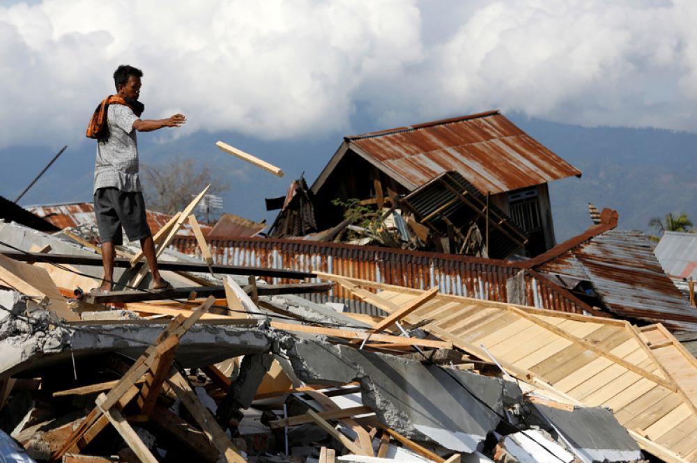 Мужчина у руин своего дома, пострадавшего от землетрясения и цунами в Палу, Индонезия.