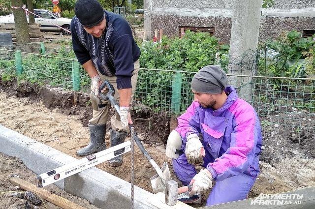 На ул. Тобольской ремонтируют квартал. Рабочие делают бордюр.