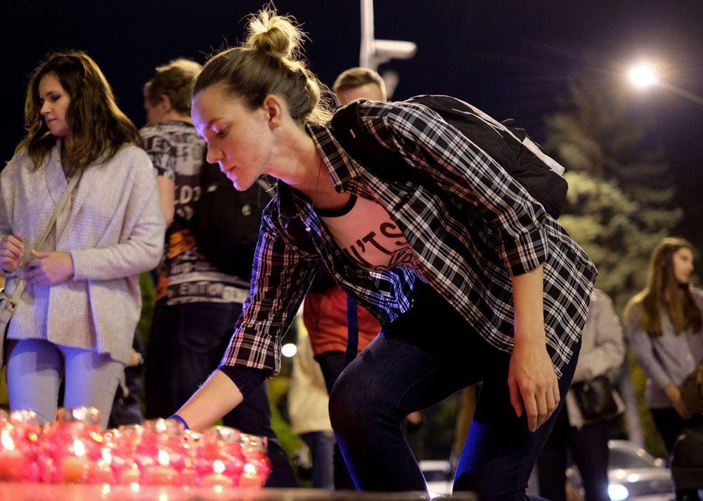 Жители Краснодара возлагают лампадки к импровизированному мемориалу во время акции памяти о погибших при нападении на керченский колледж.
